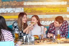 Grupa szczęśliwi przyjaciele ma lunch w restauracji, młode kobiety dzieli plasterek pizza podczas gdy uśmiechający się czas wpóln zdjęcia stock