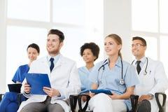 Grupa szczęśliwe lekarki na konwersatorium przy szpitalem Zdjęcia Stock