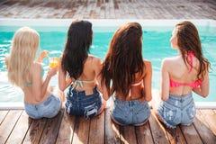 Grupa szczęśliwe młode kobiety pije koktajle blisko pływackiego basenu fotografia stock