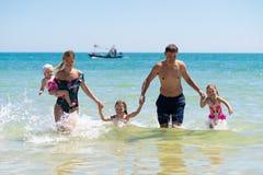 Grupa szczęśliwi dzieci bawić się i bryzga w morze plaży Dzieciaki ma zabawę outdoors Wakacje i zdrowy zdjęcie royalty free