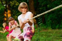 Grupa szczęśliwi dzieci bawić się zażartą rywalizację outside na trawie Dzieciaki ciągnie arkanę przy parkiem Obóz letni zdjęcie royalty free