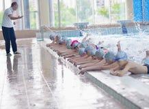 Grupa szczęśliwi dzieciaków dzieci przy pływackim basenem Obraz Stock