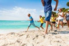 Grupa szczęśliwi dzieciaki biega na białej piasek plaży fotografia stock