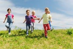 Grupa szczęśliwi dzieciaki biega outdoors Zdjęcie Royalty Free