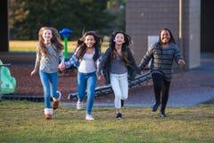 Grupa szczęśliwi dzieciaki biega outside fotografia stock