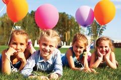 Grupa szczęśliwi dzieciaki z balonami Zdjęcia Royalty Free