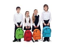 Grupa szczęśliwi dzieciaki z schoolbags szkoły pojęcie - z powrotem Zdjęcia Royalty Free
