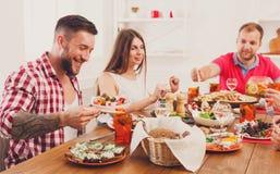 Grupa szczęśliwi ludzie przy świątecznym stołowym obiadowym przyjęciem fotografia stock