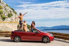 Grupa szczęśliwi ludzie w czerwonym odwracalnym samochodzie Fotografia Stock