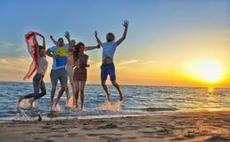 Grupa szczęśliwi młodzi ludzie biega na tle zmierzchu morze i plaża zdjęcia stock