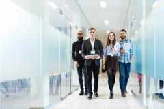Grupa szczęśliwi młodzi ludzie biznesu chodzi w biurze wpólnie zdjęcia stock