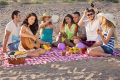 Grupa szczęśliwi młodzi ludzie ma pinkin na plaży Zdjęcia Stock