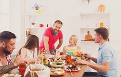 Grupa szczęśliwi młodzi ludzie przy obiadowym stołem, przyjaciele bawi się zdjęcia royalty free