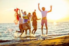 Grupa szczęśliwi młodzi ludzie tanczy przy plażą na pięknym lato zmierzchu zdjęcie royalty free