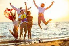 Grupa szczęśliwi młodzi ludzie tanczy przy plażą na pięknym lato zmierzchu fotografia royalty free