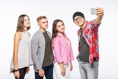Grupa szczęśliwi młodzi nastolatków ucznie bierze selfie fotografię odizolowywającą na bielu zdjęcia royalty free