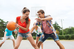 Grupa szczęśliwi nastolatkowie bawić się koszykówkę Fotografia Royalty Free