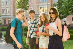 Grupa szczęśliwi nastolatkowie 13, 14 roku chodzi wzdłuż miasto ulicy, przyjaciele wita each inny przy spotkaniem obraz stock