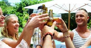 Grupa szczęśliwi przyjaciele wznosi toast piwne butelki przy outdoors grillem i szkła bawimy się zbiory