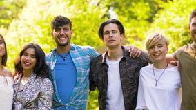 Grupa szczęśliwi uśmiechnięci przyjaciele przy lato parkiem zbiory