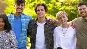 Grupa szczęśliwi uśmiechnięci przyjaciele przy lato parkiem zbiory wideo