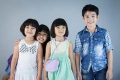 Grupa Szczęśliwy azjatykci dziecko na szarym tle zdjęcie stock