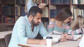 Grupa szczęśliwych uczni czytelnicze książki i narządzanie egzamin w bibliotece zdjęcie wideo