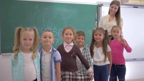 Grupa szkół podstawowych dzieci z młodym pedagogiem jest uśmiechnięta i spojrzenie przy kamerą na tle blackboard zbiory wideo