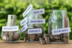 Grupa szklane słój butelki z pełnym monety i banknotu labe obraz stock