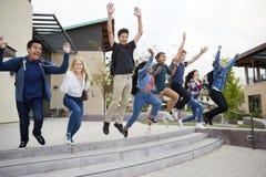 Grupa szkoła średnia ucznie Skacze W Lotniczych Outside szkoła wyższa budynkach zdjęcia stock