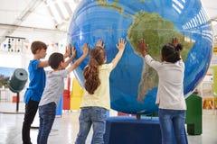 Grupa szkoła żartuje mienie gigantyczną kulę ziemską przy nauki centre fotografia stock