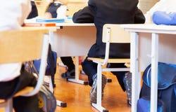 Grupa szkoła żartuje obsiadanie i słuchanie nauczyciel w classr fotografia stock