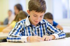 Grupa szkoła żartuje writing test w sala lekcyjnej Obraz Stock