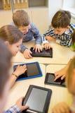 Grupa szkoła dzieciaki z pastylka komputerem osobistym w sala lekcyjnej Fotografia Stock