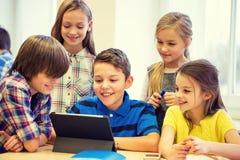 Grupa szkoła dzieciaki z pastylka komputerem osobistym w sala lekcyjnej obrazy royalty free