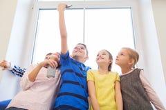 Grupa szkoła dzieciaki z smartphone i sodowaną puszką Zdjęcia Royalty Free