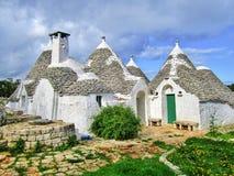 Grupa Trulli z symbolami, tradycyjnymi starymi domami i starą kamienną ścianą w Puglia, Włochy obrazy stock