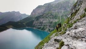Grupa trzy mężczyzna halnego arywisty przetrawersowywa odsłoniętego rockowego wypust wysokiego nad piękny turkusowy halny jezioro zdjęcie royalty free