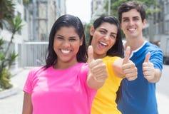Grupa trzy młodzi ludzie stoi w kreskowych i pokazują kciukach w kolorowych koszula Zdjęcia Royalty Free
