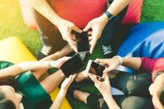 Grupa trzy młodzi ludzie używa smartphones, nowożytnego styl życia lub technologia komunikacyjna gadżetu pojęcie wpólnie, Obraz Stock
