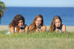Grupa trzy nastolatek dziewczyny pisać na maszynie na telefonu komórkowego lying on the beach na trawie Obrazy Royalty Free