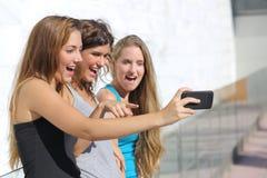 Grupa trzy nastolatek dziewczyny zadziwiał oglądać mądrze telefon Obrazy Stock
