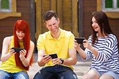 Grupa trzy przyjaciela bawić się mobilną wideo grę outdoors, dziewczyn wi fotografia royalty free