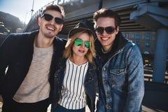 Grupa trzy przyjaciela ma zabawę i śmia się przy ulicą zdjęcia royalty free