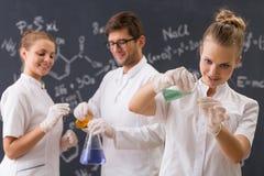 Grupa trzy ucznia prowadzi eksperyment obraz stock