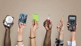 Grupa trzyma komputerowe elektronika ręki rozdziela na brown tle fotografia royalty free