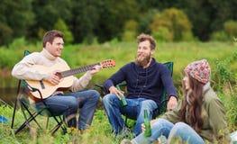 Grupa turyści bawić się gitarę w campingu Zdjęcia Royalty Free