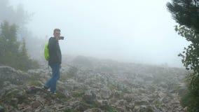 Grupa turyści chodzi wzdłuż ponurej mgłowej góry zakrywającej z lasem zbiory