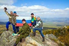 """Grupa turyÅ›ci przy wierzchoÅ'kiem halny Yalangas w poÅ'udniowych Urals z RosyjskÄ… flagÄ… paÅ""""stowowÄ… zdjęcia royalty free"""