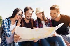Grupa turyści siedzi w parku na ławce Wpólnie patrzeją światową mapę i decydują gdzie iść następnie, Zdjęcie Stock